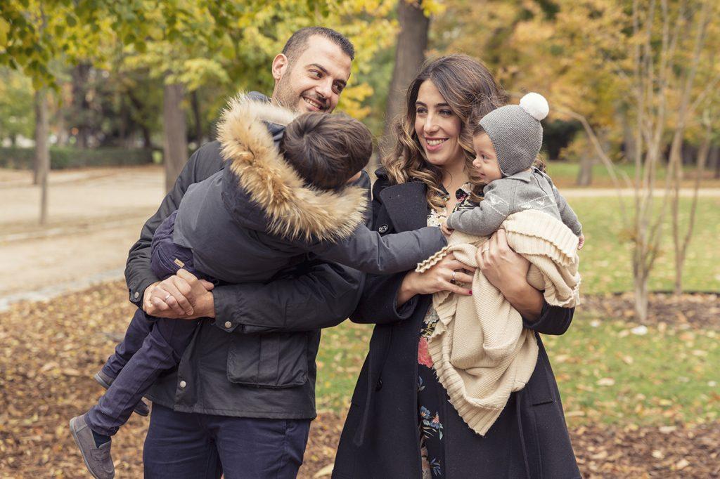Padres sujetan en brazos a sus dos hijos, están en un reportaje de bautizo en exteriores, en el Parque del Retiro de Madrid. Es invierno y llevan abrigos negros.