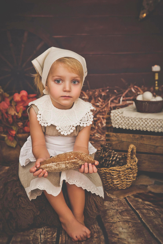 Niña sentada en un taburete de pelo, lleva un pañuelo blanco en la cabeza y sujeta un pan entre sus manos. Esta en un decorado de pastorcilla en una sesión de fotos de Navidad en Madrid.