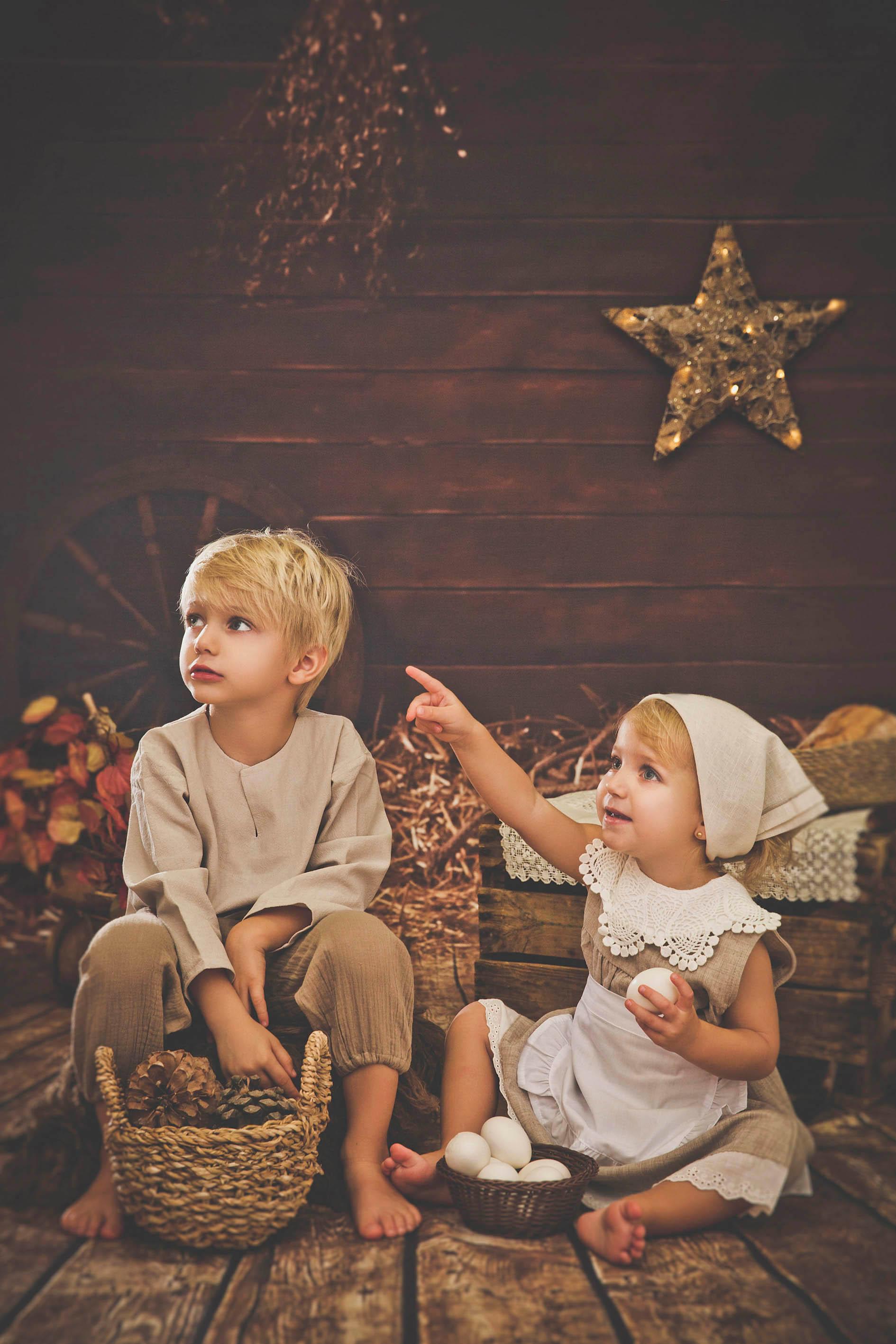 Hermanos vestidos de pastorcillos sentados en el suelo, tienen un huevo en la mano y piñas en otra, miran y señalan algo que les ha llamado la atención, imagen realizada con una oferta de navidad.