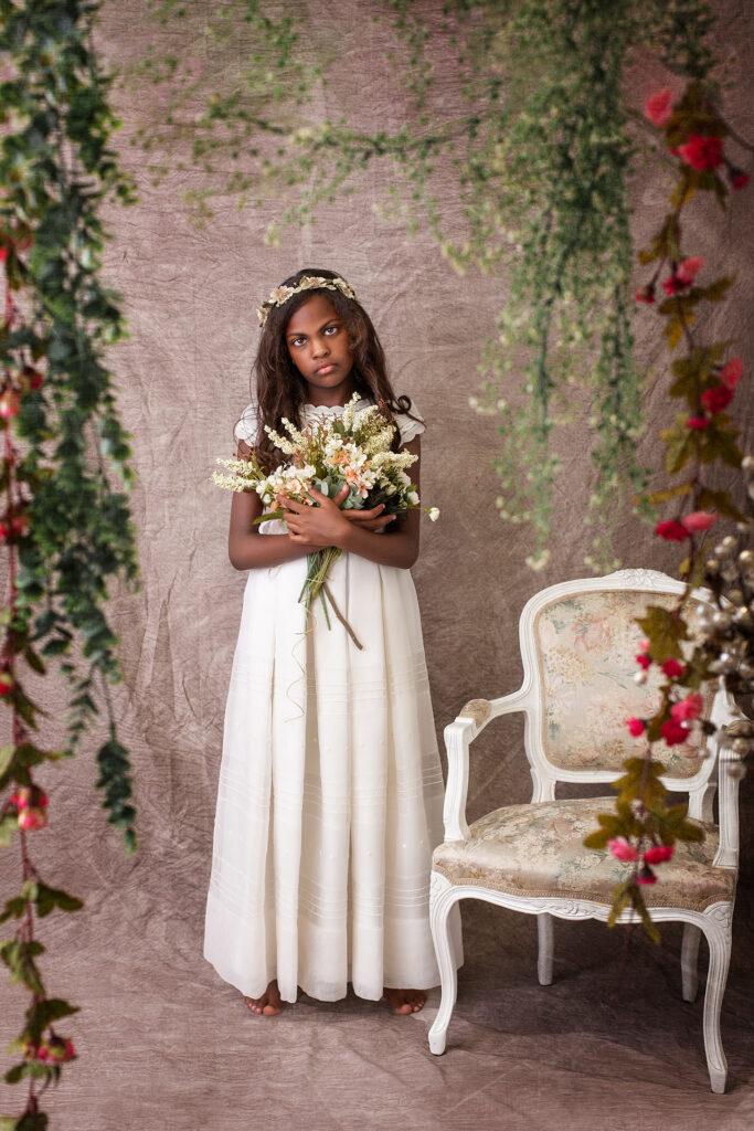Sesión de Primera Comunión en estudio, niña con un vestido blanco, tiene unas flores entre los brazos, a su lado tiene una silla de madera y cuelgan plantas alrededor de la imagen.
