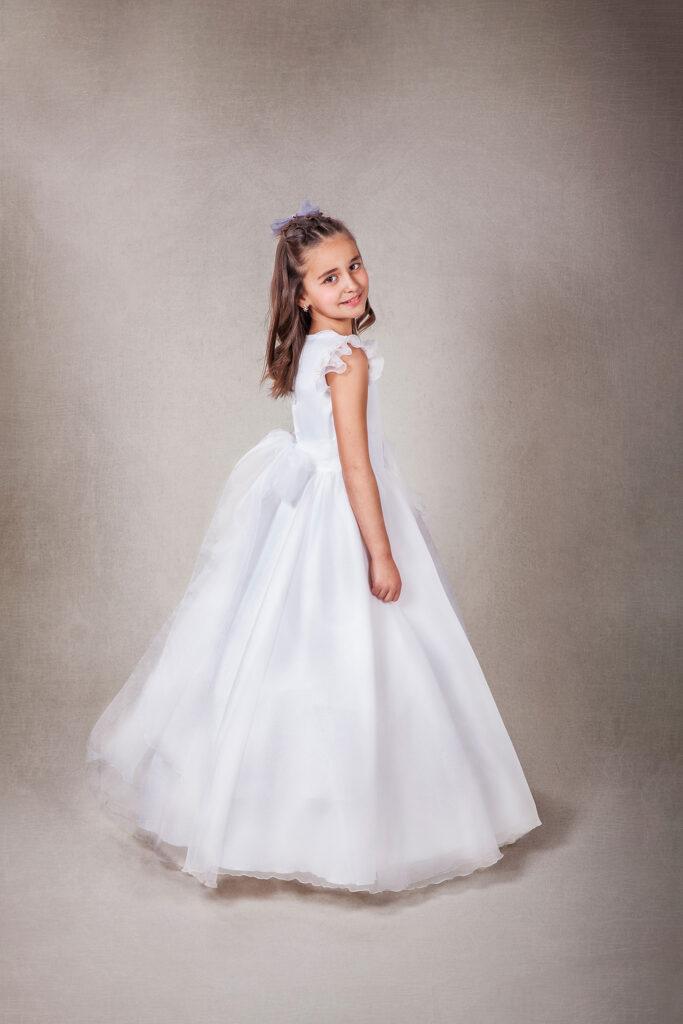Sesión de comunión en estudio, niña con vestido blanco posa en un estudio de fotografía.